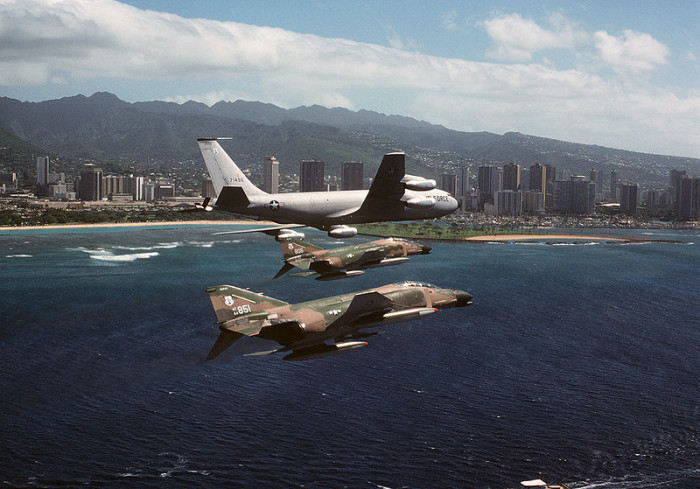 13. Two United States Air Force aircraft fly in formation with a Boeing KC-135A of the Arizona Air National Guard, with the Honolulu Skyline in the background.