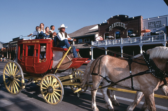7. They're riding a stagecoach around the Jackson Hole Town Square.