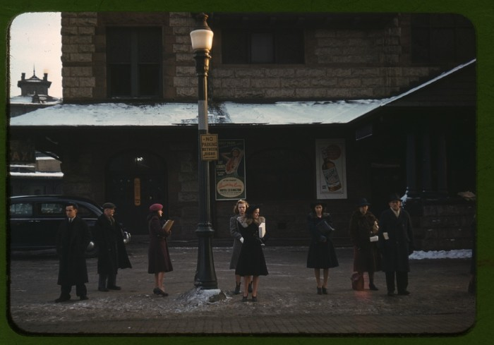 13. A group of commuters just off the train, waiting for the bus to go home in Lowell, Massachusetts. (1940)