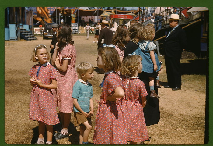8. A gaggle of children at the Vermont state fair, Rutland.  Some families did have the means to spend a day amusing themselves among the attractions, rides, and vendors of fairs and carnivals. (1940)