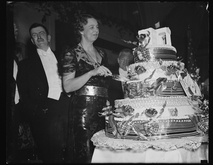 17. Mrs. Roosevelt cuts the enormous birthday cake for President Roosevelt during one of his birthday balls. (1938)