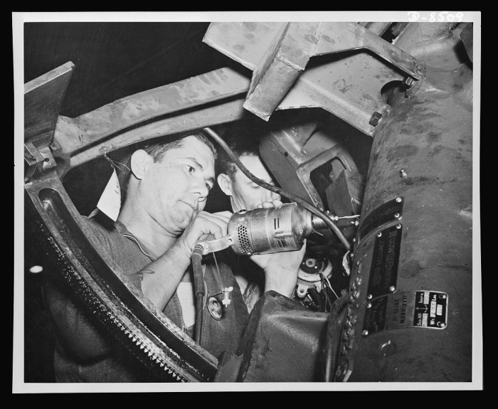 7. A first class machinist from Ohio, Andrew S. Horn is photographed working on intricate wiring for a ship's gun, along with R.V. Presby, a Tennessee native and first class electrician.