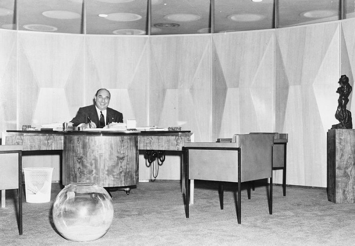 12. A prominent real estate agent sits in his New York circular office in 1952.