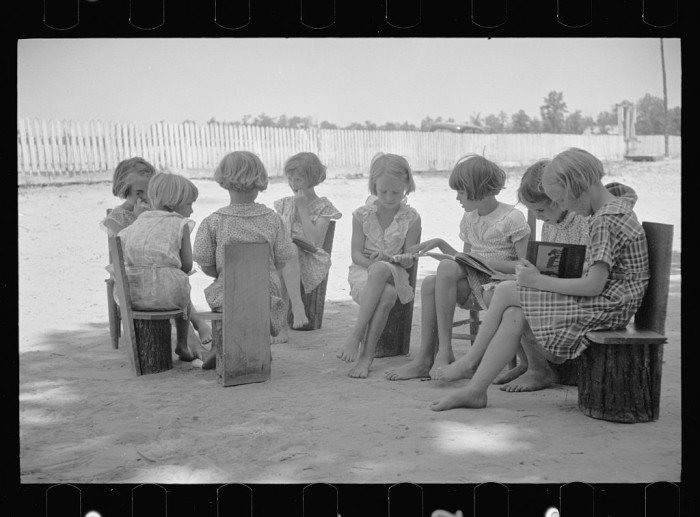 6. A school scene at Cumberland Mountain Farms near Scottsboro, Alabama in June 1936. Their make-shift chairs and lack of shoes speak to their simple lifestyle.
