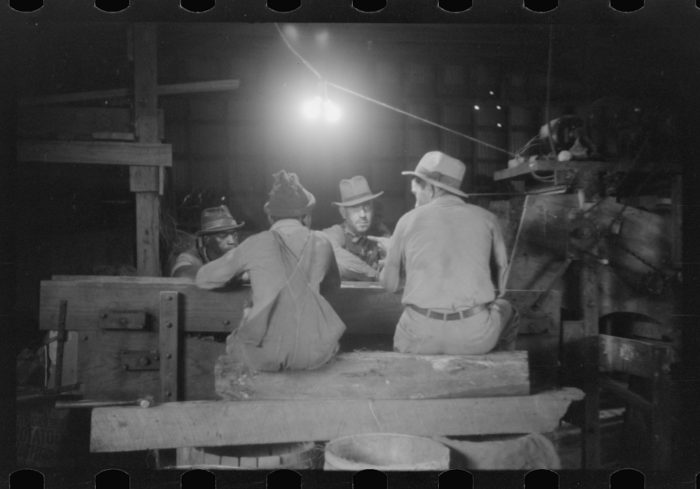 8. Four men sit at the pick table end of a potato grader. Although they were working, they did have some good conversations.
