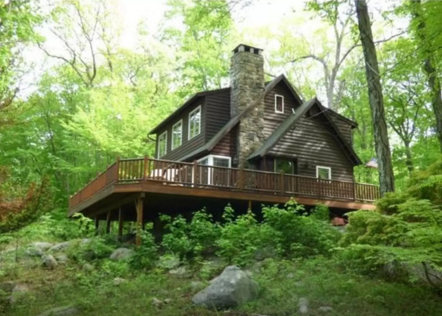 9. This cabin in the woods offers that classic wooden interior and a huge pit hangout for all your friends.
