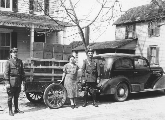 13. The Delaware State Police force was founded in 1923. Here, two DSP troopers stand with a woman and her trailer of chickens in Seaford.