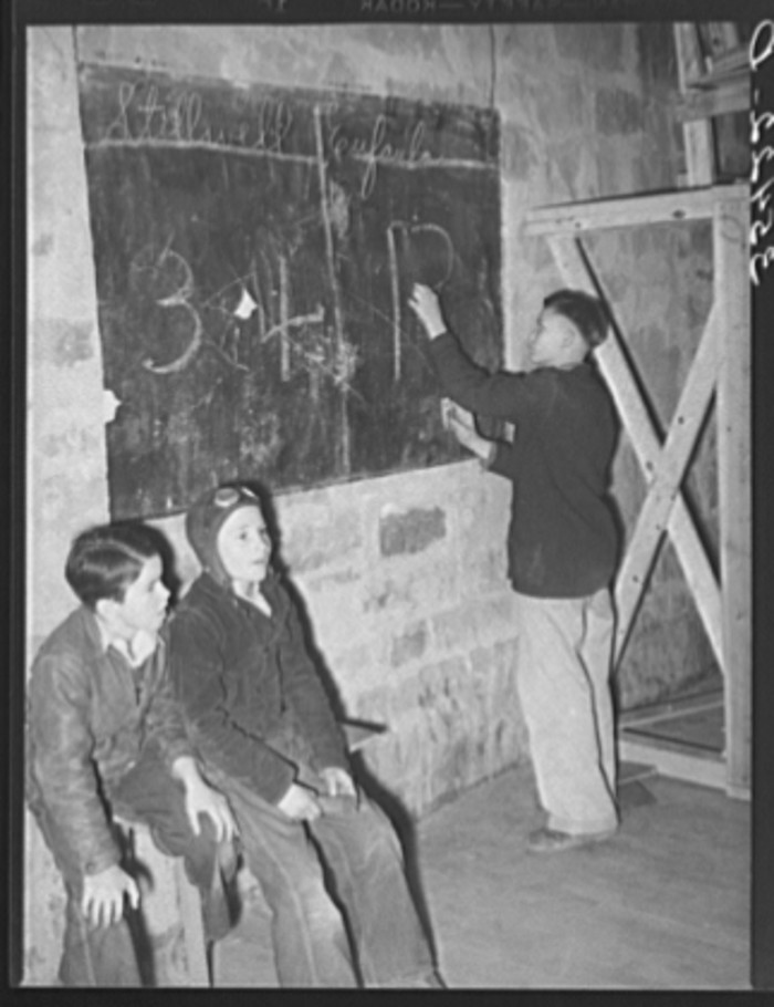 8. With no electric scoreboards, these high school students are marking up the score on a blackboard for a basketball game between Eufaula and Stillwell High School. Taken in 1940.