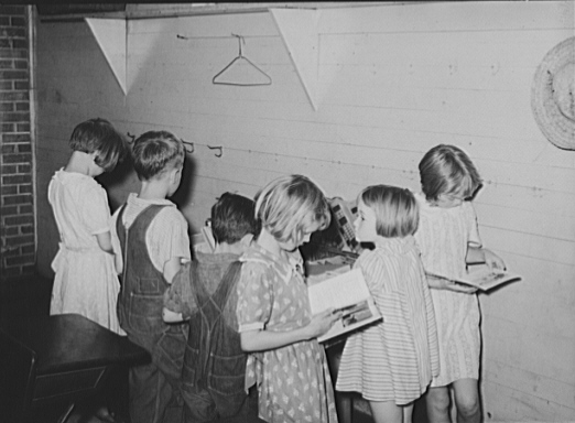 9.Children choosing books from the small school library near La Forge, August 1938.
