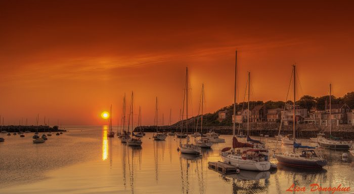 10. A hazy orange sunset over Rockport harbor fills the entire scene with a warm, copper glow.