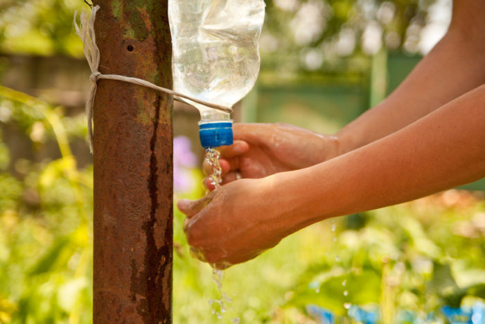 6. An upside-down bottle with holes in the lid makes a perfect camping-ready hands washing station.