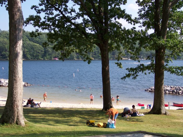 The lake boasts a sizable beach, perfect for sunbathing next to the calm water.