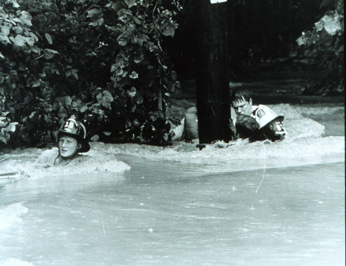9. Firefighters rescuing a man during extreme flash floods in Rockville in July 1975.