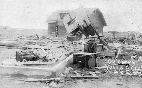 """View of the debris caused by a tornado in Yuma (Yuma County), Colorado. Shows men, an overturned safe, a wagon on its side, bricks and a damaged barn."""