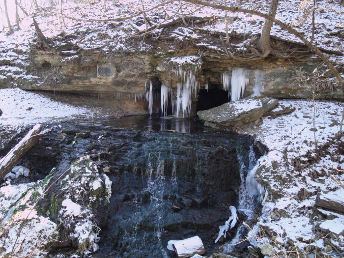 The natural spring runs through the cave and spills out over the rocks in the front.