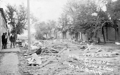 """...a street full of debris, wood panels, downed trees, an automobile and brick buildings..."""