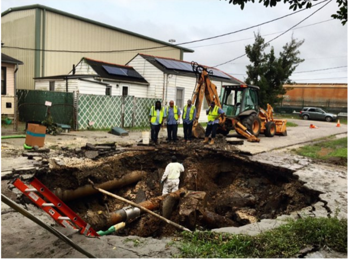 Because of heavy rains, the hole that they dug to fix the pipe began to fill with water and a huge sinkhole developed at the site.