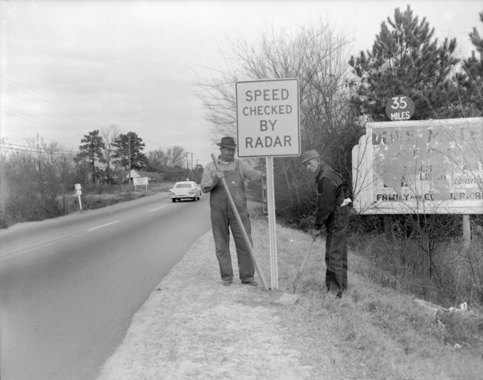 """1. Workers place a """"Speed Checked by Radar"""" sign along US21 north of Columbia in 1962. (Oh joy....)"""