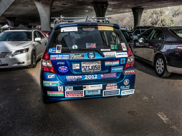 4. The back bumper of that car is covered in stickers.