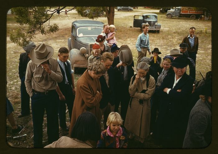 4. A crowd saying grace before a barbeque was served at a Pie Town, New Mexico fair. That's a 1935 Ford parked in the background.