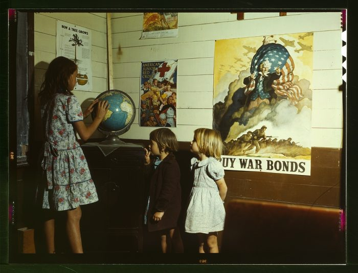 11. Rural schoolchildren learn geography in a school room plastered with patriotic posters.