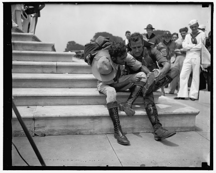 12. These two Venezuelan Boy Scouts walked 800 miles to attend a Boy Scout Jamboree in Washington D.C. Here, they are examining their boots after trudging 25 miles a day for two years in order to arrive on time on January 11, 1935. Rafael Petit, left and Juan Carmona, right.