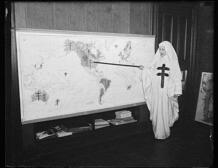 """18. Tuberculosis """"battle map,"""" shown by Mildred Showalter of Washington D.C., dressed as the Spirit of the Double-barred cross of the anti- tuberculosis movement. She points to places where war is being waged against the """"White Plague."""""""
