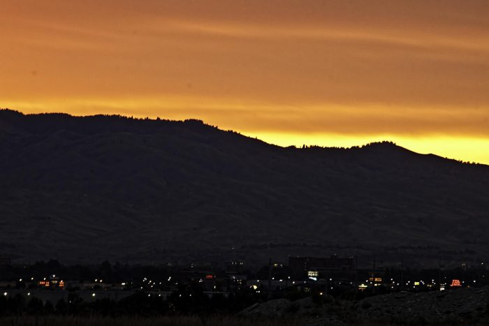10. A vibrant sunrise meets the the darkened cityscape in this photo.