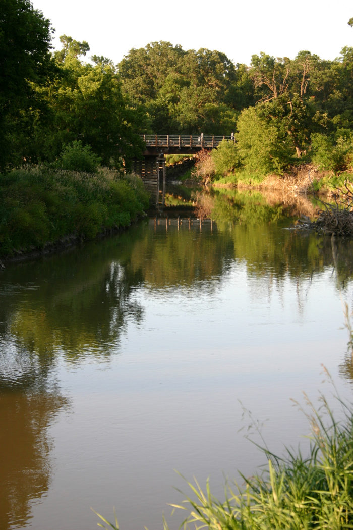 5. A serene shot of a bridge in Fort Ransom State Park reflecting into the waters of the Sheyenne River