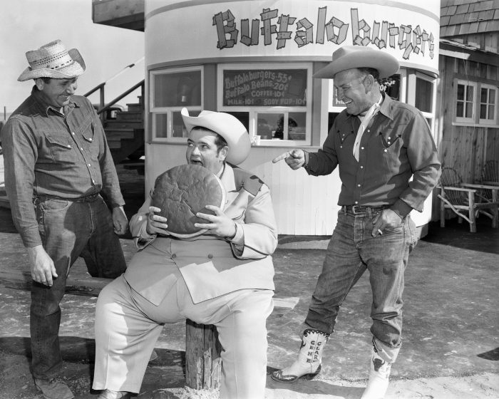 9. A giant buffalo burger is devoured by radio DJ Texas Tiny in front of Buffalo Ranch in Newport Beach circa 1955.