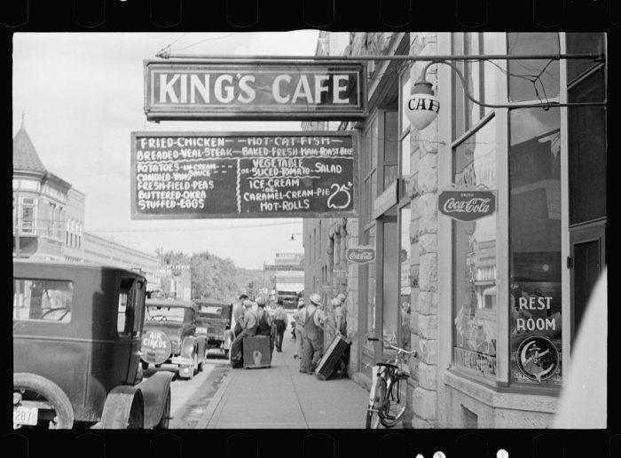 21. A street scene in Clarksville, Arkansas. Menu items include fresh field peas, stuffed eggs, sliced tomato salad, potatoes in cream, buttered okra, and caramel cream pie.