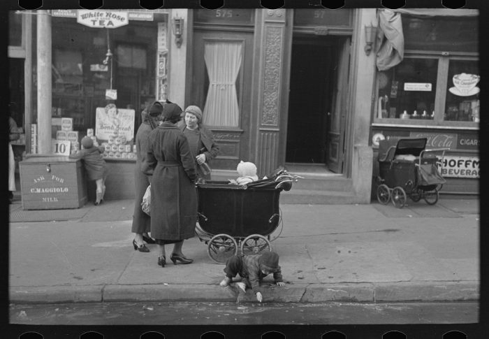 7. Mothers talking together while a child plays in the gutter on 139th Street just east of St. Anne's Avenue, Bronx, New York City.