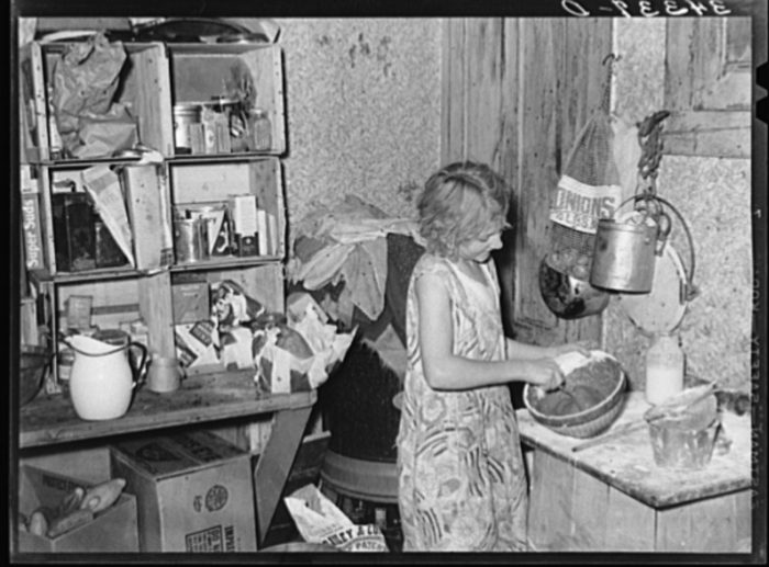 9.  Daughter of FSA (Farm Security Administration) client mixing a cake on a farm near Bradford, in Orange County.