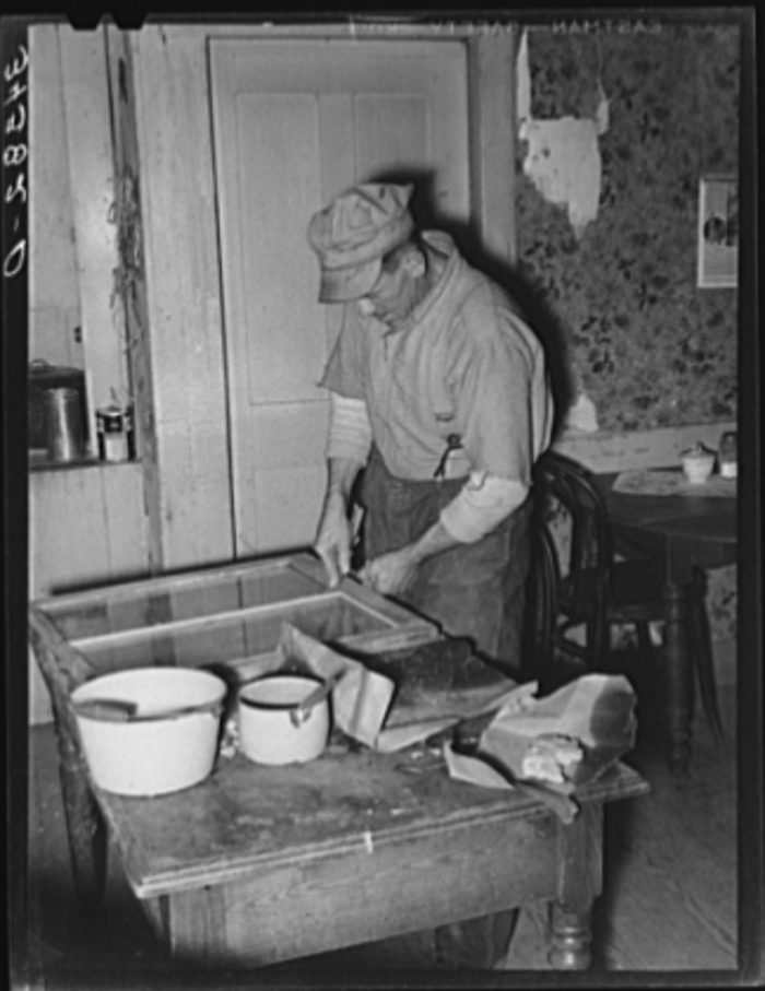 11.  Farmer puttying window glass in his house.