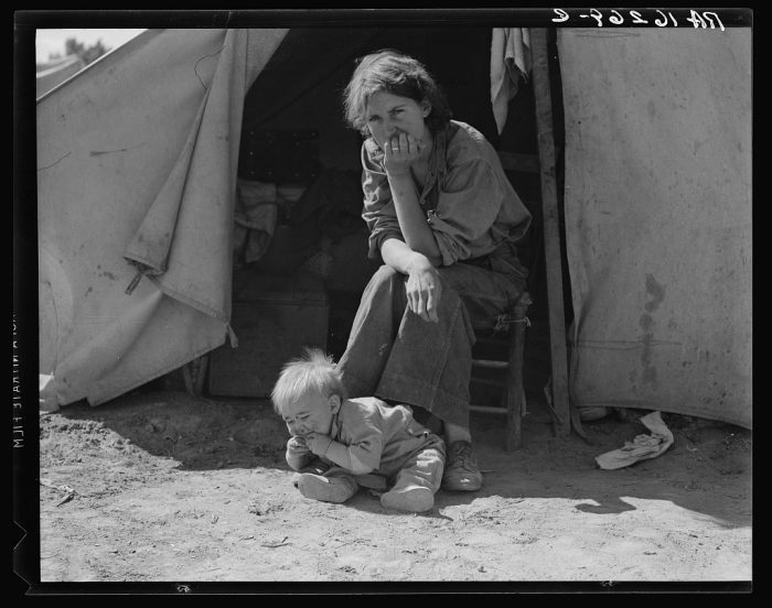4. An eighteen year-old mother from Oklahoma, now a California migrant. She sits listlessly with her young child near the family's tent. (1939)
