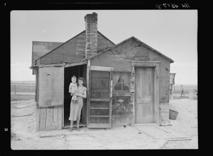 5. A patchwork homesteader's house, made from whatever materials at hand, and a couple of its residents. 1936