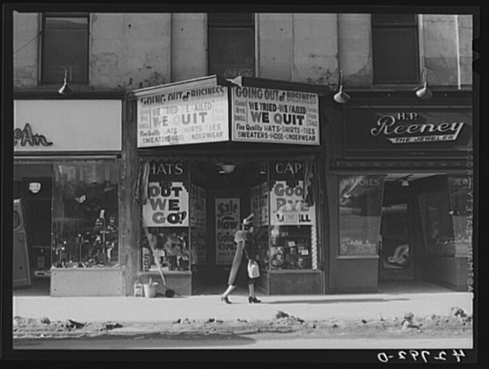 """13. A store going out of business in Lowell. Note the """"Out We Go"""" signs."""