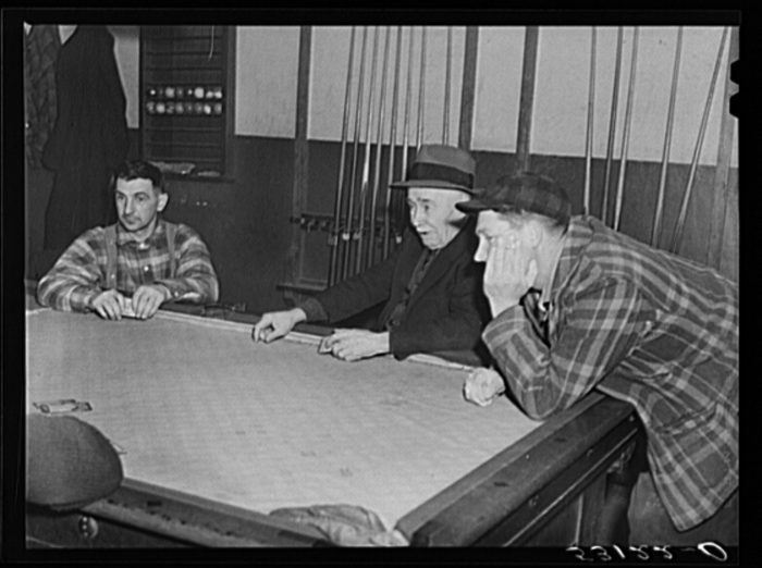 13.  Farmers playing cards in the pool room in town on a winter morning.