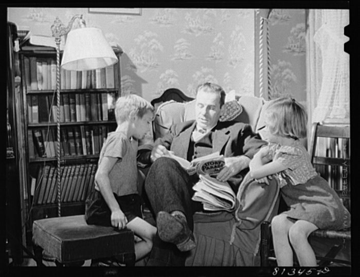 17. A father reading to his children in Williamstown.