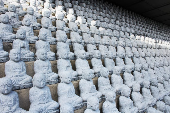 Tucked away into a quiet corner between the main hall and memorial hall is the Garden of Ji Jang Bosal. where more than a thousand miniature figurines of disciples sit peaking over the ledge.