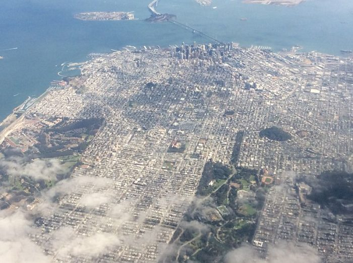 10. The city looks especially magical above the wispy clouds here. This view is taken from the west, with Golden Gate Park on the bottom and the Bay Bridge at the top.