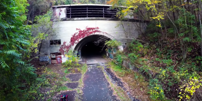 The video dives into the shadowy tunnels of the abandoned road.