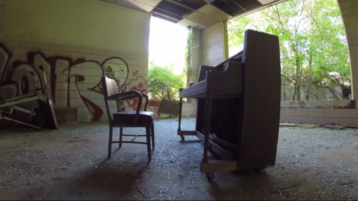 An eerie piano and chair boldly stand in the middle of this room.