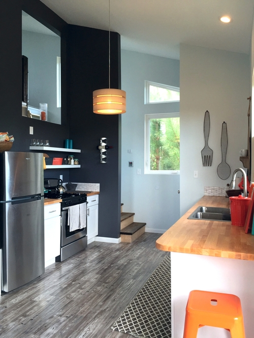 With butcher block countertops, pergo flooring, a double sink, and mini dishwasher, it's safe to say nothing was spared in the tiny home's kitchen.