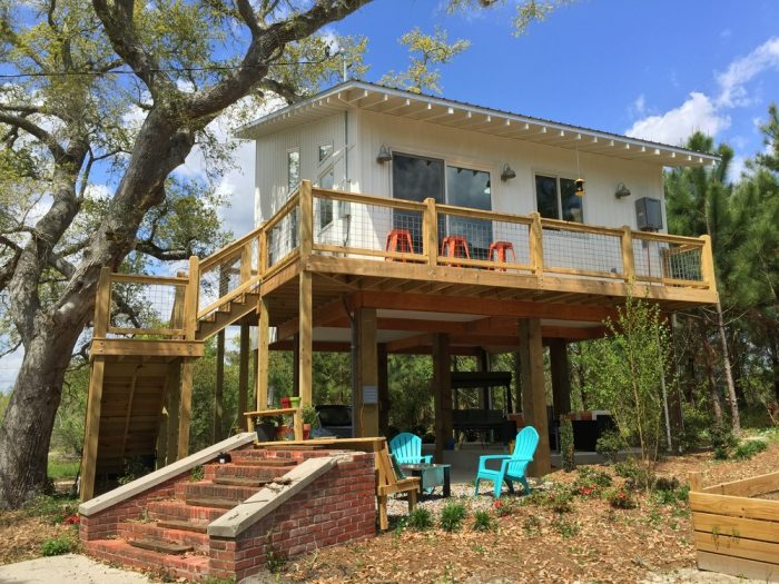 The energy efficient home uses solar panels for heating, while the live oak provides plenty of shade.