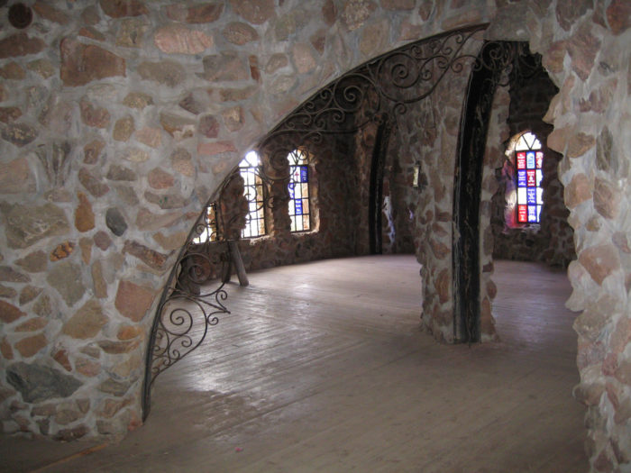The inside of the castle is just as stunning as the outside and features exquisite arches (pictured), colorful stained glass, and iron stairs throughout.