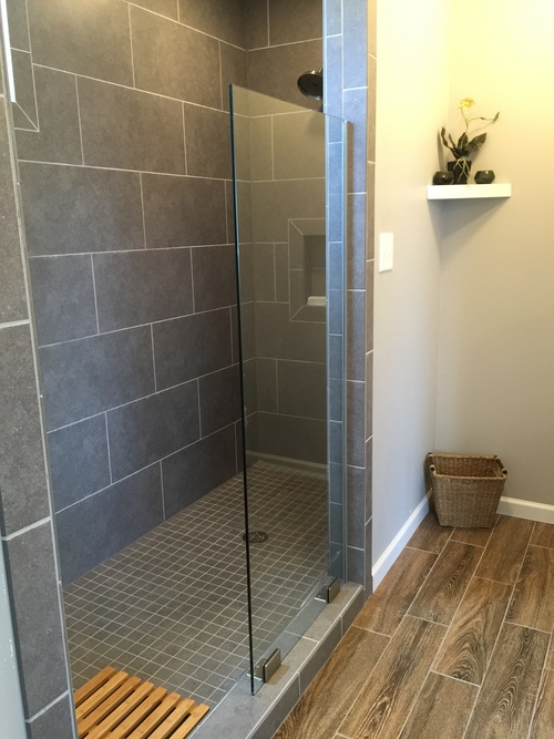 The spa-like bathroom includes a 6' walk-in shower, beautiful tiling, and wood accents.