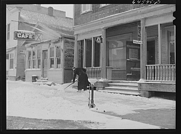 5. Store owner shoveling snow outside of his business in Hettinger, North Dakota. 1942