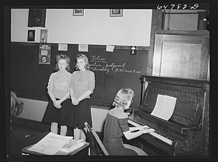 "7. This photograph taken in Epping was captioned, ""High school girls singing 'Remember Pearl Harbor' at meeting of the women of the town to promote sale of defense bonds and stamps."" 1942"