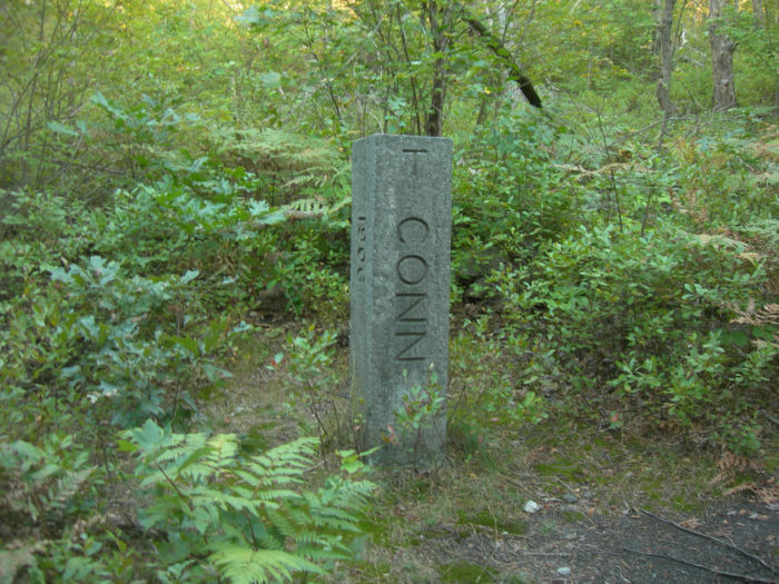 The line was envisioned as a straight trip from New York City to Boston, but the expensive cost of building through mountains and over water eventually lead to abandonment. Stones mark the state line where the trail then continues in to Massachusetts.